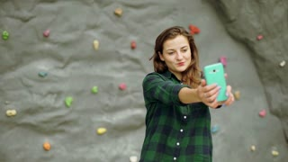 Girl standing against climbing wall and doing selfies