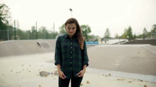 Girl standing in skate park and smiling to the camera