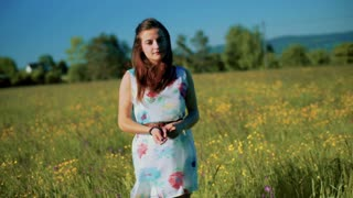 Girl standing in the meadow and looking to the camera