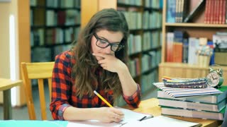 Girl studying in the library and looking very tired