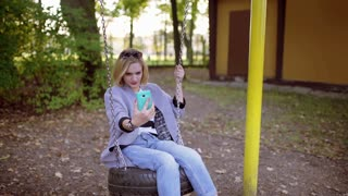 Girl swinging on the seesaw and doing selfies on smartphone