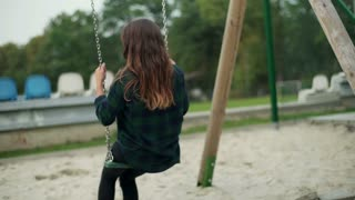 Girl swinging on the seesaw and smiling to the camera