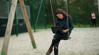 Girl swinging on the seesaw with laptop and smiling to the camera