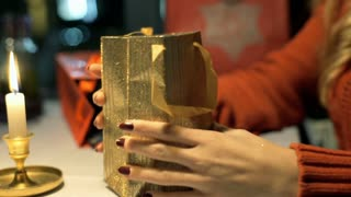Girl takes golden watch from a festive bag and checks it