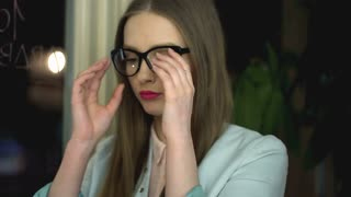 Girl taking off glasses and massage her head because of headache