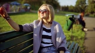 Girl taking off sunglasses in the park and smiling to the camera