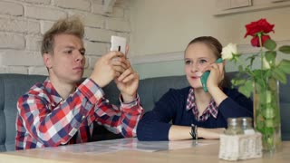 Girl talking on cellphone and boy texting sms in the restaurant