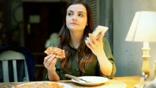 Girl talking on cellphone while eating pizza in the cafe
