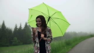 Girl talking on loudspeaker and holding green umbrella