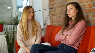 Girl talking to her offended friend while sitting at home