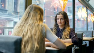 Girl tells something shocking to her best friend in the festive cafe, steadycam