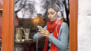 Girl texting messages on smartphone while listening music and drinking coffee, s