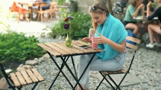Girl texting on smartphone and drinking cocktail in the outdoor cafe