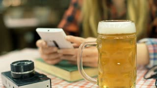 Girl texting on smartphone in the cafe and drinking beer, steadycam shot