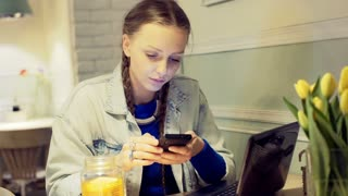 Girl texting on smartphone in the cafe and drinking tea