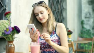 Girl texting on smartphone in the outdoor cafe and smiling to the camera