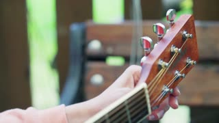 Girl touching tuning keys and tune the guitar
