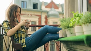 Girl using cellphone and smiling to the camera on the balcony