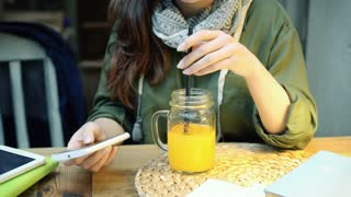 Girl using smartphone and mixing beverage in the restaurant