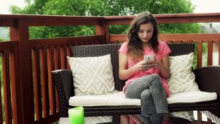 Girl using smartphone and relaxing on the deck