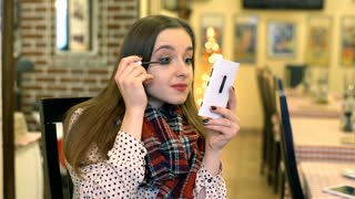 Girl using smartphone as a mirror and putting mascara on eyelashes, steadycam sh