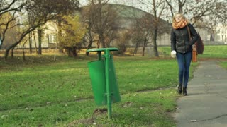 Girl walking on pathway in the park and throwing coffee cup into trashcan