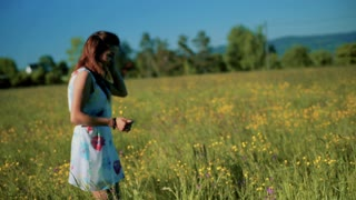 Girl walking on the meadow and picking flowers