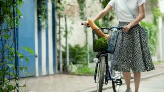 Girl walking with her bicycle and checking shopping in the basket, steadycam sho