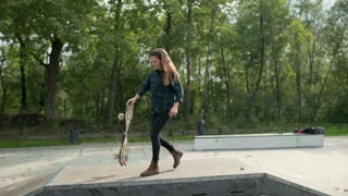 Girl walking with skateboard and smiling to the camera