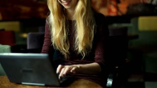 Girl wearing glasses and finish using laptop in the cafe, steadycam shot