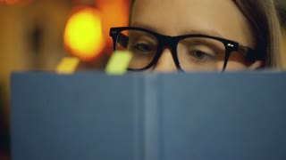 Girl wearing glasses and reading book in the cafe