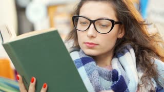 Girl wearing glasses and reading book while sitting outdoors