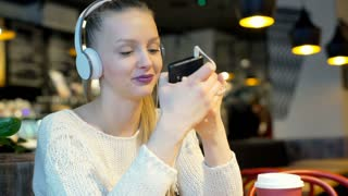 Girl wearing headphones and watching something funny on smartphone, steadycam sh