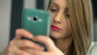 Girl with pink lips sitting in the cafe and texting on smartphone