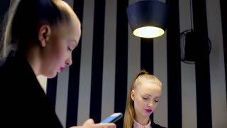 Girl with ponytail standing next to the mirror and browsing internet on smartpho
