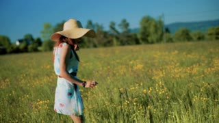 Girl with straw hat walking on the meadow and picking flowers