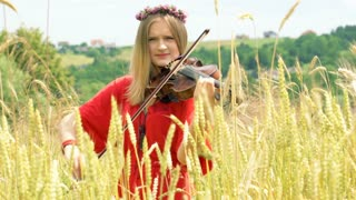 Girl with wreath of flowers playing on violin and smiling to the camera
