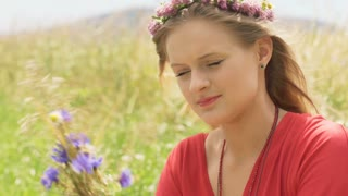 Girl with wreath picking field flowers and looking absorbed, steadycam shot