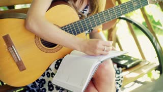 Girl writing music in her notebook and trying to play on guitar