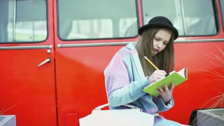 Girl writing on her journal and smiling to the camera