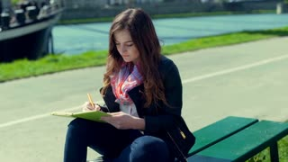 Girl writing something in her journal and smiling to the camera
