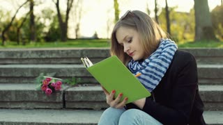 Girl writing something in notebook and relaxing in the park