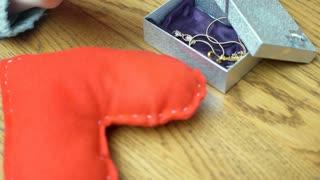 Girl's hands touching present and handmade heart, steadycam shot