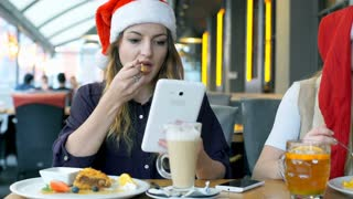 Girls in Santa's hats eating desserts and using electronics, steadycam shot