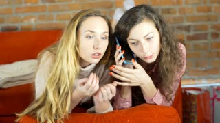 Girls lying on the sofa and talking with someone on one cellphone