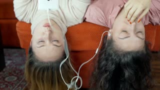 Girls lying with their heads down and listening music, steadycam shot