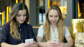 Girls sitting in the cafe and browsing internet on smartphones, steadycam shot