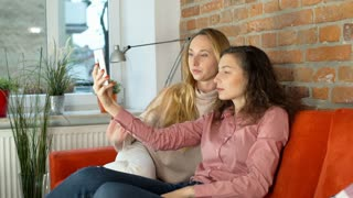 Girls sitting on the sofa and doing photos on smartphone