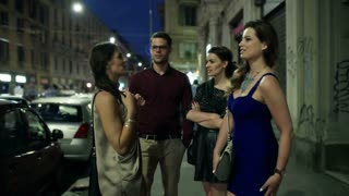 Group of people talking in the city at night, steadycam shot