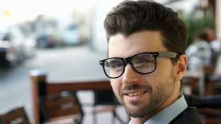 Handsome businessman wearing glasses and talking to someone